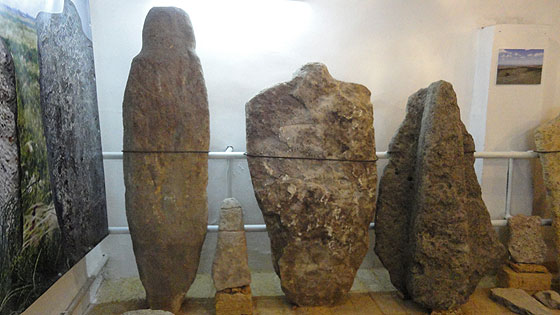 Фалоїдний камінь (ліворуч) та людиноподібна стела (в центрі) епохи міді-бронзи і кіммерійська скульптура (праворуч)