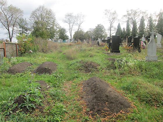 Могила пророка Івана Деркача (на передньому плані) на кладовищі у селі Космирин Бучацького району